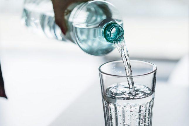 Woda z misja z butelki nalewana do szklanki